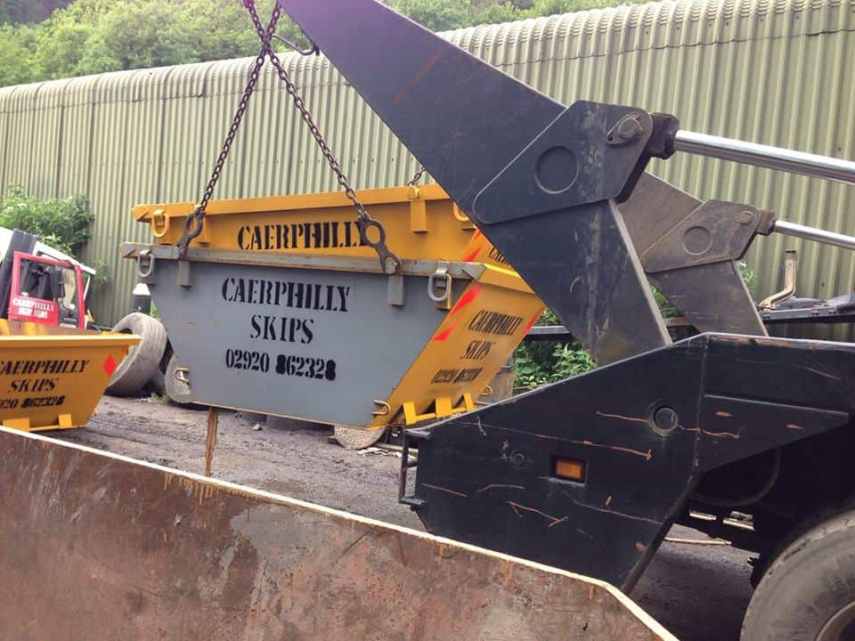 skips being lifted onto skip truck