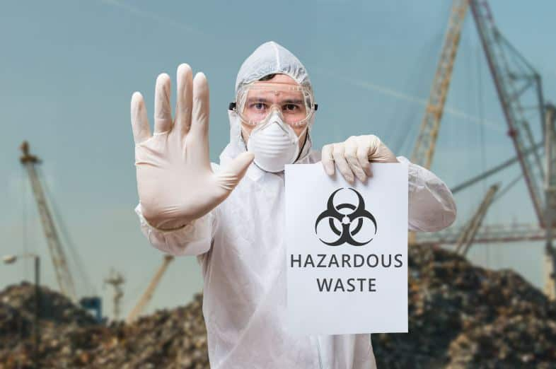 hazardous waste sign being held up by worker